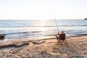 Abenteuer Fischwasser Fischer am Strand mit Sonnenuntergang